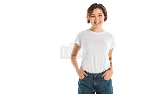 smiling young woman with hands in pockets looking at camera isolated on white