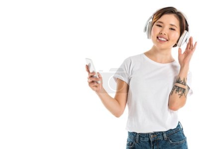 smiling young woman wearing headphones, listening music and using smartphone isolated on white