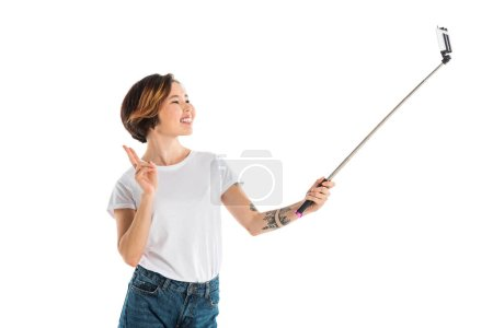 Photo pour Belle jeune femme souriante tenant selfie sur smartphone à l'aide du bâton de selfie isolé sur blanc - image libre de droit