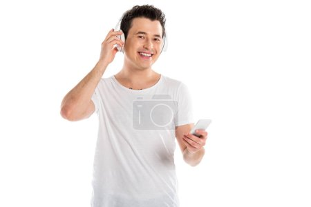 handsome man in headphones listening to music and using smartphone isolated on white