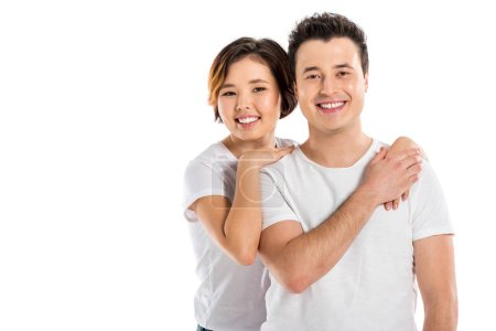 smiling portrait of young loving couple hugging and looking at camera isolated on white