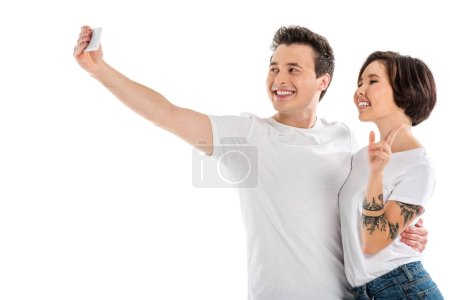 cheerful couple taking selfie on smartphone isolated on white