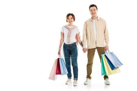 smiling couple looking at camera, holding hands and carrying shopping bags isolated on white