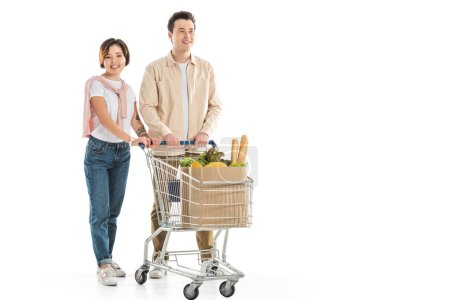 Photo for Happy young couple with shopping cart full of groceries looking at camera isolated on white - Royalty Free Image
