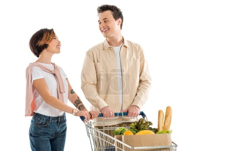 smiling young couple with shopping cart full of groceries looking at each other isolated on white