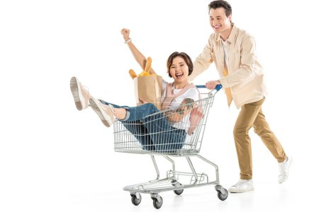 Photo pour Mari souriant en poussant le caddie avec femme à l'intérieur tenue d'épicerie isolée sur couple blanc, s'amuser - image libre de droit