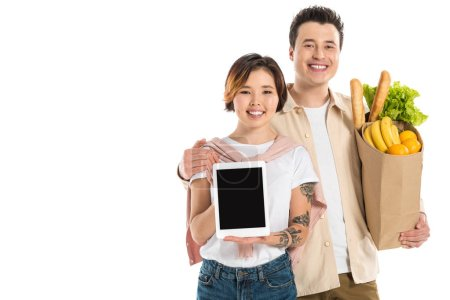 Photo for Smiling husband holding grocery bag while wife presenting digital tablet with blank screen isolated on white - Royalty Free Image