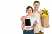 smiling husband holding grocery bag while wife presenting digital tablet with blank screen isolated on white