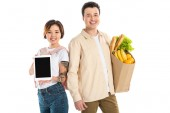 happy husband holding grocery bag while wife presenting digital tablet with blank screen isolated on white