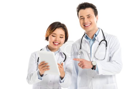 Photo for Smiling female and male doctors using digital tablet isolated on white - Royalty Free Image