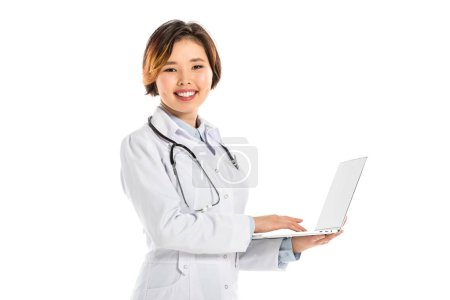female doctor in stethoscope looking at camera and holding laptop isolated on white