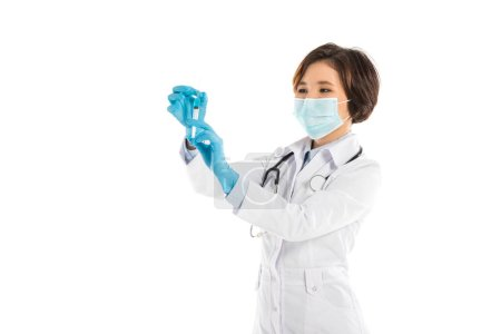 concentrated female doctor in medical mask holding syringe isolated on white