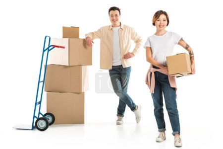 smiling couple looking at camera with cardboard boxes isolated on white, moving to new house concept