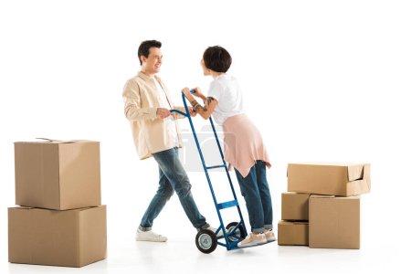 Foto de Explotación esposo en el carro de mano con cajas de cartón en el fondo, hacia el nuevo concepto de casa - Imagen libre de derechos