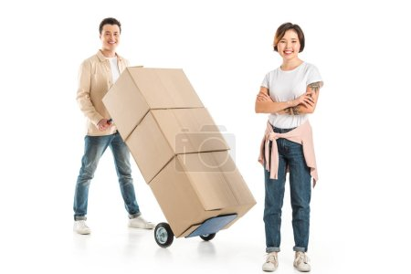 Photo for Husband carrying hand truck with cardboard boxes on background while wife looking at camera, moving to new house concept - Royalty Free Image