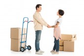 husband and wife holding hands with cardboard boxes on background, moving to new house concept