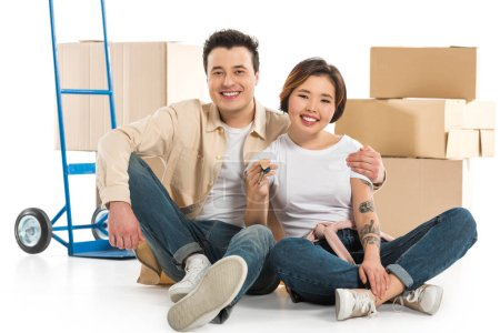 Photo for Couple hugging and holding keys with cardboard boxes on background, moving to new house concept - Royalty Free Image