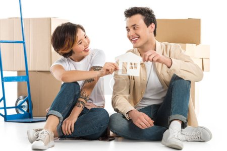 Photo for Couple looking at each other and holding house model with cardboard boxes on background, moving to new house concept - Royalty Free Image