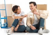 couple looking at each other and holding house model with cardboard boxes on background, moving to new house concept