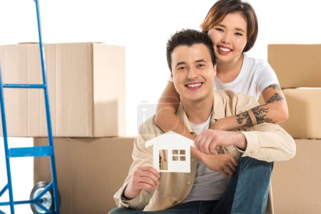 Photo for Couple hugging and holding house model with cardboard boxes on background, moving to new house concept - Royalty Free Image