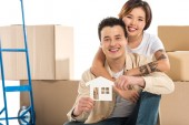 couple hugging and holding house model with cardboard boxes on background, moving to new house concept