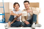 husband and wife holding house model with cardboard boxes on background, moving to new house concept