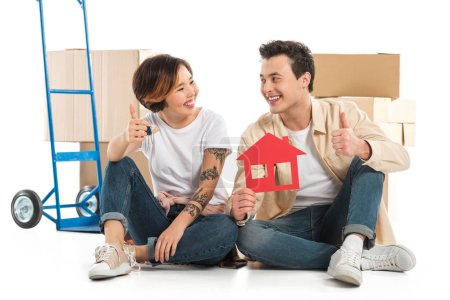 Photo for Couple showing thumbs up signs and holding house model, moving to new house concept - Royalty Free Image