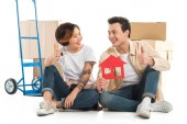 couple showing thumbs up signs and holding house model, moving to new house concept