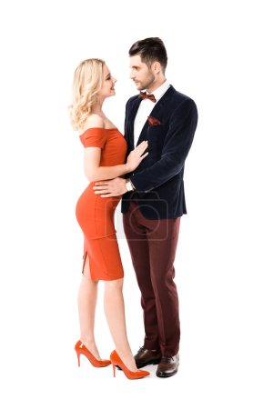 Beautiful couple of blonde woman in red dress and man in suit hugging isolated on white