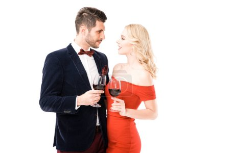 Beautiful couple clinking glasses with red wine while looking at each other isolated on white