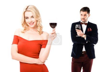 Atractiva pareja joven sosteniendo copas de vino rojo aislado en blanco