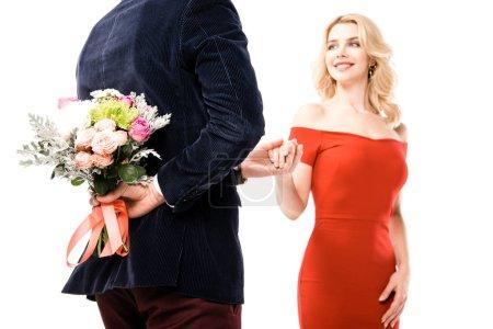 Photo pour Vue arrière de l'homme tenant de belles fleurs derrière le dos pour une jolie petite amie isolée sur blanc - image libre de droit
