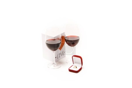 Photo for Two glasses with red wine, lovely postcard with heart and ring box isolated on white - Royalty Free Image