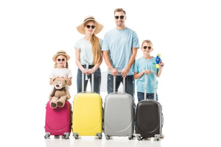 Happy family standing with colourful luggage and smiling isolated on white