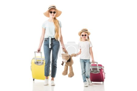 Mother and daughter holding teddy bear and baggage isolated on white