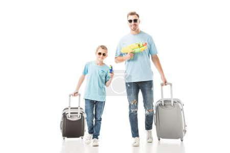 Dad and son walking with luggage and holding water guns isolated on white