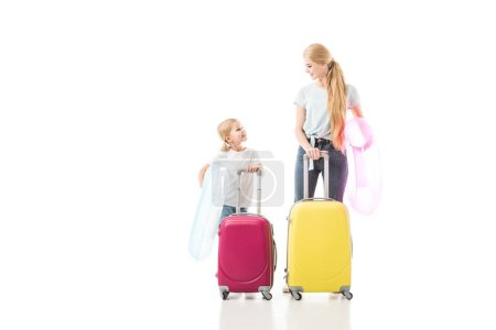 Mother and daughter smiling and holding baggage isolated on white