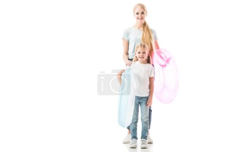 Mother and daughter standing with swim rings and smiling isolated on white