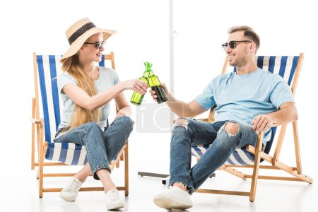 Couple sitting on deck chairs, relaxing and drinking beer isolated on white