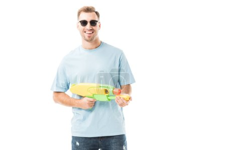 Cheerful man holding water gun and standing in sunglasses isolated on white