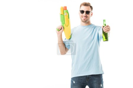 Cheerful man in sunglasses holding water gun and bottle isolated on white