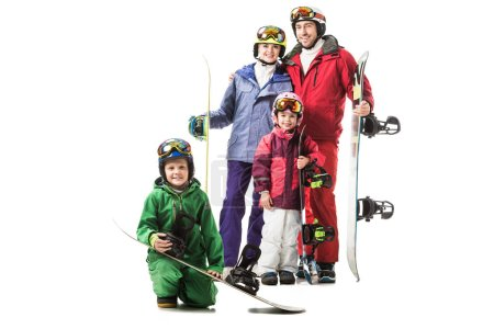 Cheerful family standing in snowsuits with snowboards and smiling isolated on white