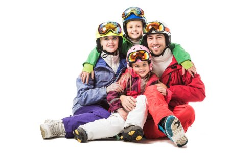 Happy family sitting and hugging in snowsuits isolated on white
