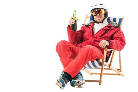 Happy man in red ski suit with beer bottle sitting in deck chair and smiling isolated on white