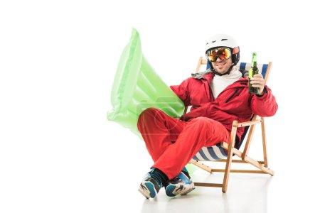 Foto de Hombre en ropa de esquí con colchón con piscina y botella de cerveza sentado en la silla de cubierta y sonrientes aislados en blanco - Imagen libre de derechos