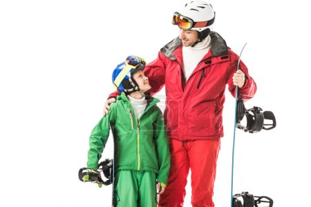 adult father in ski suit embracing preteen son with snowboard isolated on white