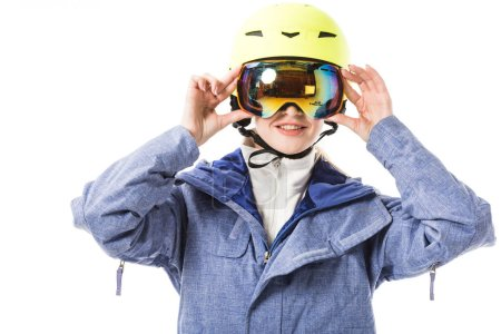young woman in blue ski jacket, goggles and helmet smiling isolated on white