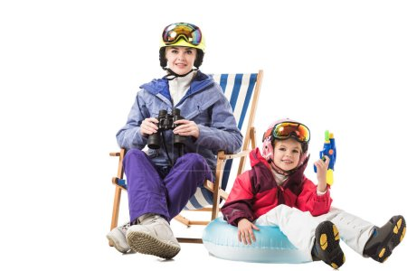 Smiling woman with binoculars sitting in deck chair while daughter with water gun looking at camera isolated on white