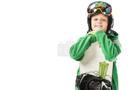 Cute preteen boy in ski suit and goggles leaning on white snowboard, smiling and looking at camera isolated on white
