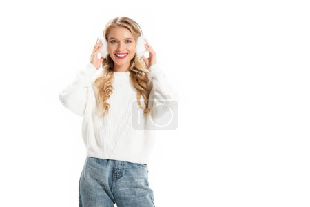 Photo for Smiling woman touching winter earmuffs isolated on white - Royalty Free Image